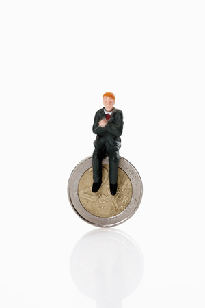 male likeness: Manager figurine sitting on euro coin Stock Photo