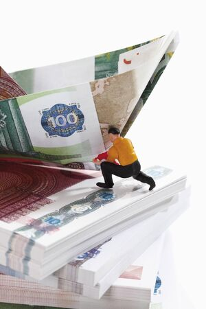 bundles: Figurine on bundles of euro notes with paper boat