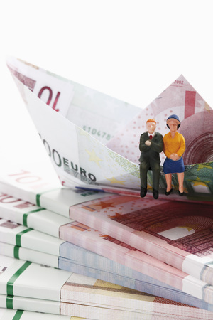 bundles: Couple figurine on bundles of euro notes with paper boat