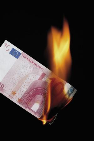 western script: 10 euro note burning against black background