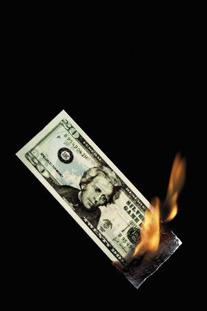 20-Dollar-Note brennt vor schwarzem Hintergrund Standard-Bild