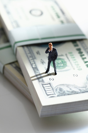 male likeness: Manager figurine standing on bundle of 100 us dollar notes