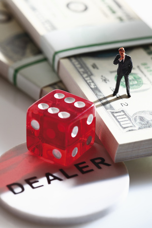 western script: Manager figurine standing on bundle of 100 us dollar notes with dice Stock Photo