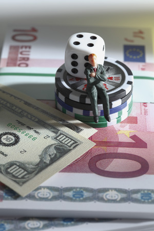 male likeness: Figurine sitting on jetons with dice and banknotes