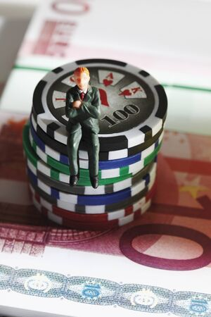 male likeness: Figurine sitting on jetons with euro banknotes, close up Stock Photo