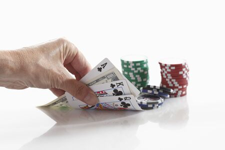 Human hand holding playing cards with gambling chips photo