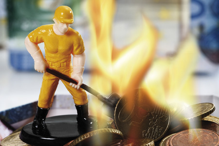 burning money: Figurine burning money, close up Stock Photo