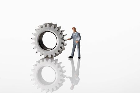 male likeness: Manager figurine standing with cogwheels on white background