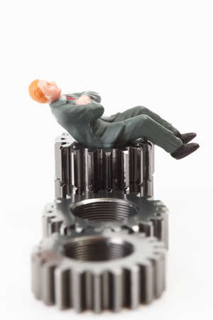 male likeness: Manager figurine relaxing on cogwheels