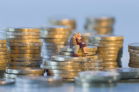 female likeness: Couple figurines sitting on coin tower and kissing Stock Photo