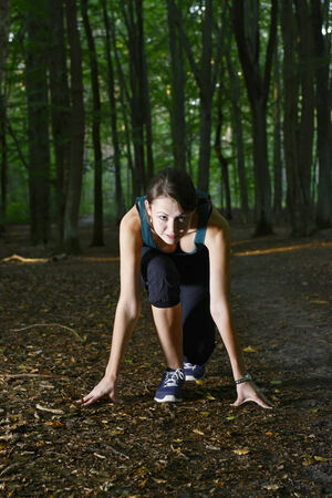 starting position: Jogging woman in starting position in forest