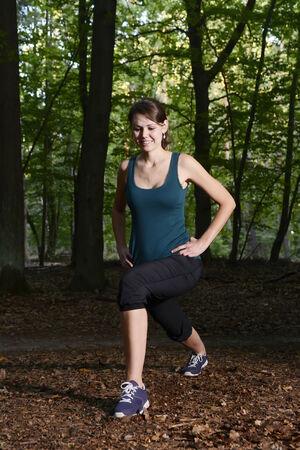 lunges: Mujer joven que calienta con estocadas para correr