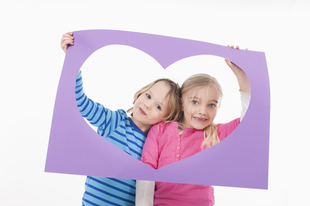 Brother and sister looking through heart shaped board photo