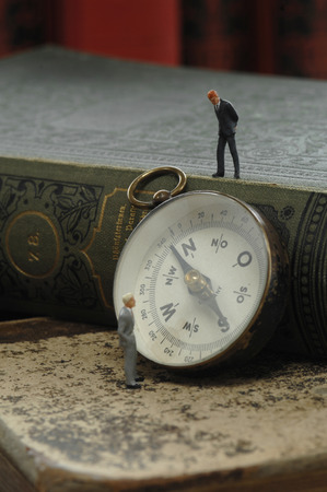 male likeness: Compass with figurine and book, close up