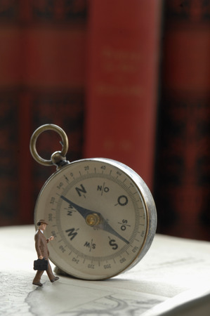 Compass and figurine on book Stock Photo