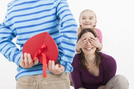 gift behind back: Daughter covering eyes of mother, Son with gift box in foreground
