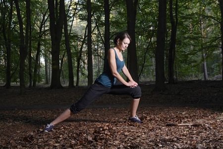 lunges: Young woman warming up with lunges for running