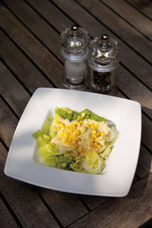 indulgence: Butterhead lettuce with sweet corn in plate with salt and pepper