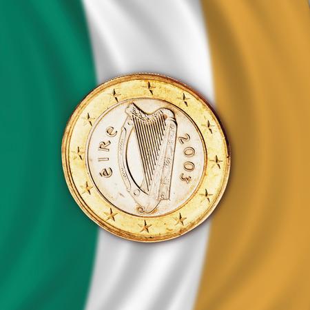 traditionally irish: Euro coin against Irish flag, close up