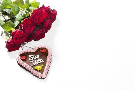 rosas rojas: Rosas rojas y el coraz�n de pan de jengibre en el fondo blanco