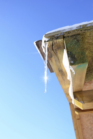 winter thaw: Icicle on roof, sunlight in winter Stock Photo