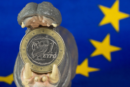 Greek one euro coin in mouth of hippo figurine