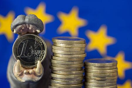 greek coins: Euro coin in mouth of hippo figurine, EU flag