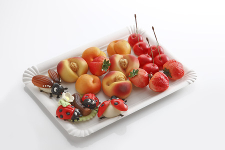 paper plates: Marzipan, ladybird, may bug, peaches, strawberries, cherries on paper plate Stock Photo