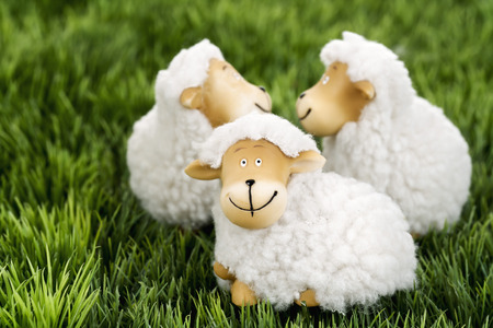 paschal lamb: Wool sheep figurines on grass Stock Photo