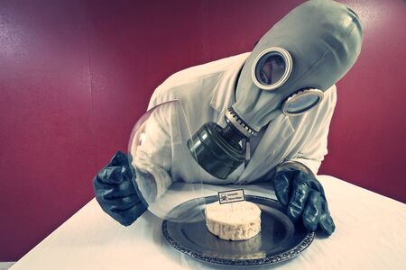 gas mask: Man in front of a plate with cheese under cheese cover