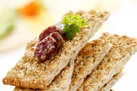 crispbread: Stacked sesame crispbread with slices of salami