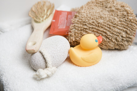 peeling rubber: Wellness, white towel with pumice stone, hairbrush, rubber duck