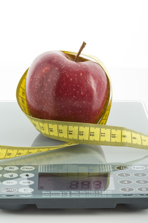 exactitude: Red apple on scales with measuring tape, dieting