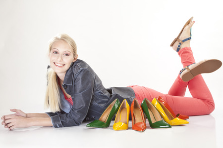 consuming: Young woman with many colorful pairs of shoes