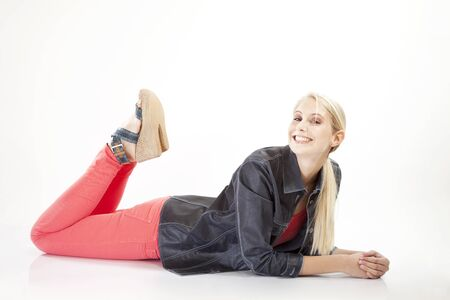 red pants: young woman in red pants lies smiling on ground