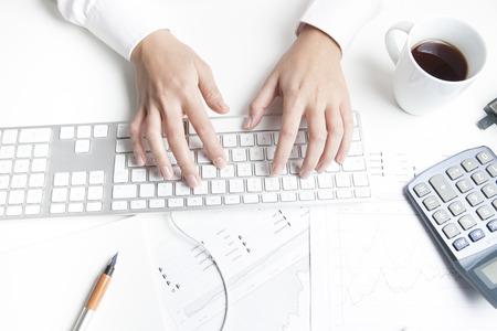 mujeres trabajando: Mujer que trabaja en el escritorio, el teclado Foto de archivo