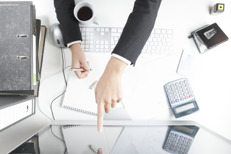 Woman working at desk, pointing on screen Stock fotó