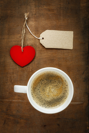 valentine day cup of coffee: Coffee cup and heart on dark wood, blank paper