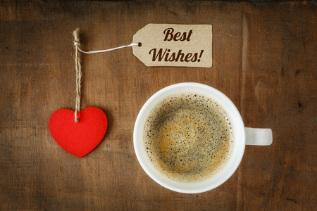 valentine day cup of coffee: Coffee cup and heart on dark wood, Best wishes