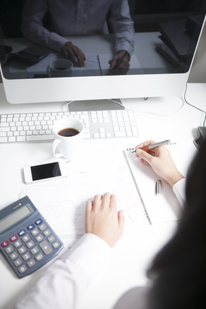 Woman working at desk, writing on notepad