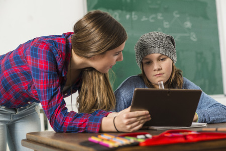 class room: Two girls in class room learning with digital tablet Stock Photo