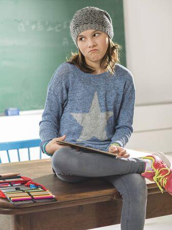 salle classe: Malheureuse assis dans la salle de classe avec tablette