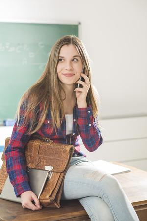 salle classe: Jeune fille assise dans la salle de classe avec tablette et t�l�phone Banque d'images