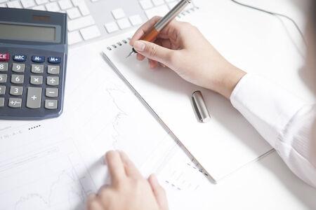 stockbroker: Stockbroker writing on notepad, calculator Stock Photo