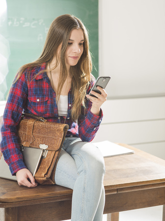class room: Young girl sitting  in class room with tablet and phone