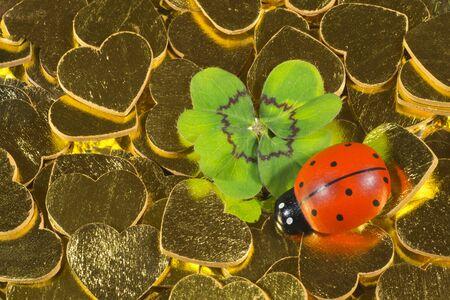 cloverleaves: Cloverleaf and ladybird figurine on golden hearts