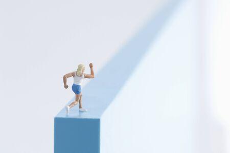 Woman figurine running on a blcck.