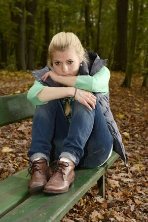 Germany, Berlin, sad young woman sitting on bench