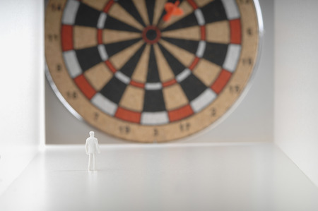 male likeness: Businessman figurine standing in front of dartboard.