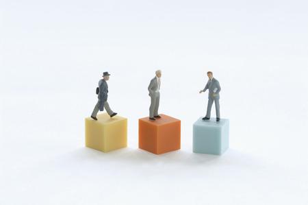male likeness: Businesspeople figurines on a podium.